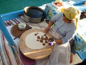 Tant som gör pannkakor med choklad i sin båt